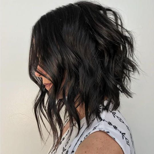 Long Angled Bob | An asymmetrical cut, a shaggy classic, and—ooh!—a fresh set of bangs. What'll you have? We like a compromise. When it comes to hair, it's about finding the sweet spot that satisfies our indecisive nature. Go super short and sassy? Or keep those locks long and lively? It's a toss-up. That's when we turn to Old Faithful: medium short haircuts. These medium length hairstyles toe the line between short and long, hitting those collarbones and striking a pose.